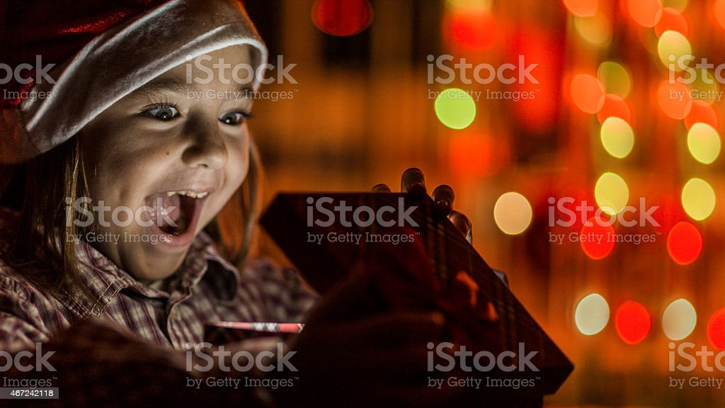 Little girl excitedly opening a gift stock photo