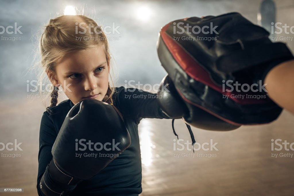 Little girl exercising boxing with unrecognizable trainer in a health club. stock photo