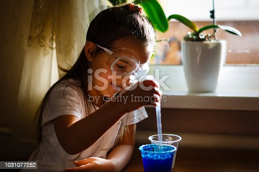 istock Little girl experimenting in elementary science class with protective gloves and glasses 1031077252