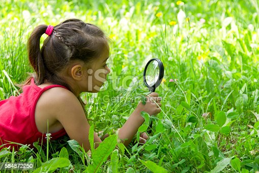 istock Little girl exploring nature looking at magnifying glass 584872250
