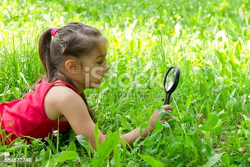 istock Little girl exploring nature with a magnifying glass 584872746