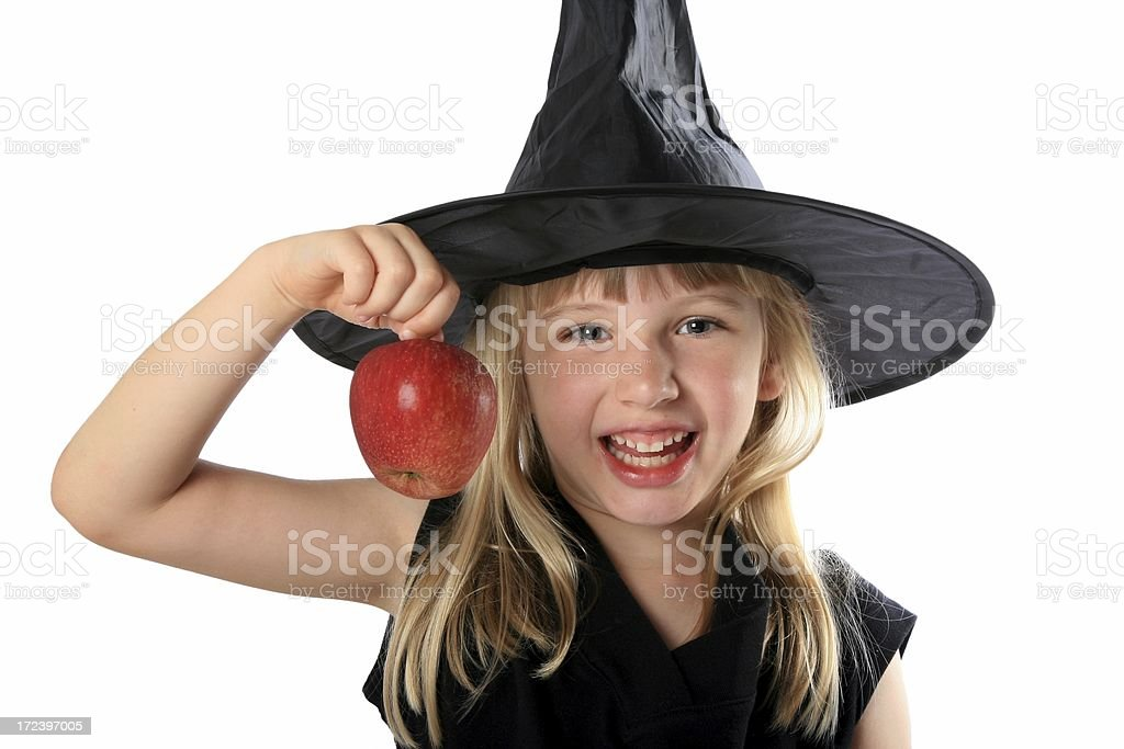 Little girl fancy dress up wicked witch holding red apple stock photo