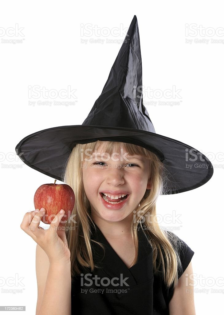 Little girl fancy dress wicked witch holding red apple stock photo