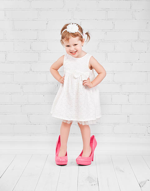 little girl fashionista in  big pink heeled shoes stock photo