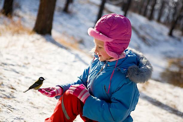 Kleines Mädchen Fütterung ein Vogel im winter-Wald. – Foto