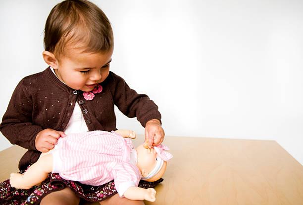 Little girl feeding baby doll stock photo