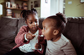 Close up of a little girl feeding her baby sister