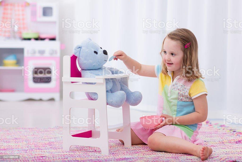Little girl feeding her toy bear foto