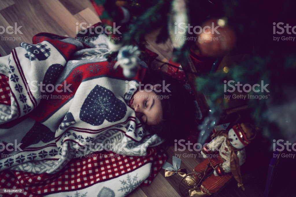 Little Girl Fell Asleep Under Christmas Tree Wile Witing for Santa stock photo