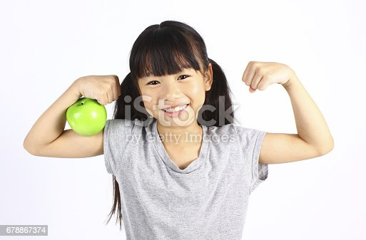 istock A little girl flexes her muscle while showing off the apple 678867374