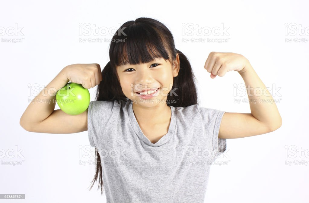 A little girl flexes her muscle while showing off the apple stock photo