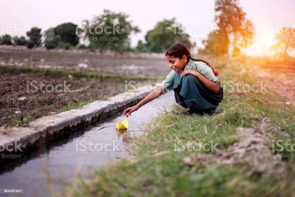 Little girl flowing paper boat in to water stock photo