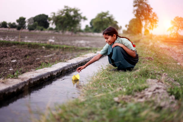 Little girl flowing paper boat in to water Little girl of elementary age wearing school uniform sitting near water canal outdoor in the field & flowing paper boat in to the water. developing countries stock pictures, royalty-free photos & images