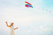 Little girl flying a kite at sky on beach, summer activities for kids