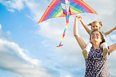 Grandmother and granddaughter having fun, playing with kite together.