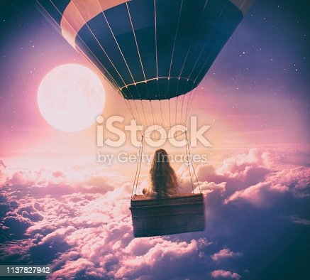 Dreamy photo manipulation of little girl flying with a hot air balloon over the clouds, looking at full moon.