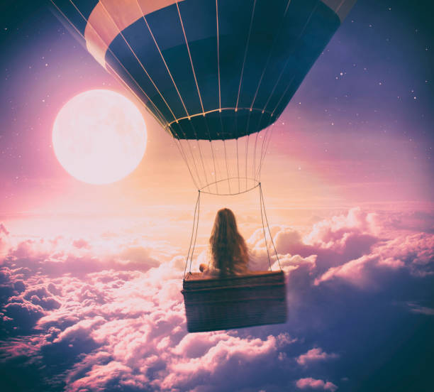 Little girl flying over the clouds Dreamy photo manipulation of little girl flying with a hot air balloon over the clouds, looking at full moon. dreamlike stock pictures, royalty-free photos & images