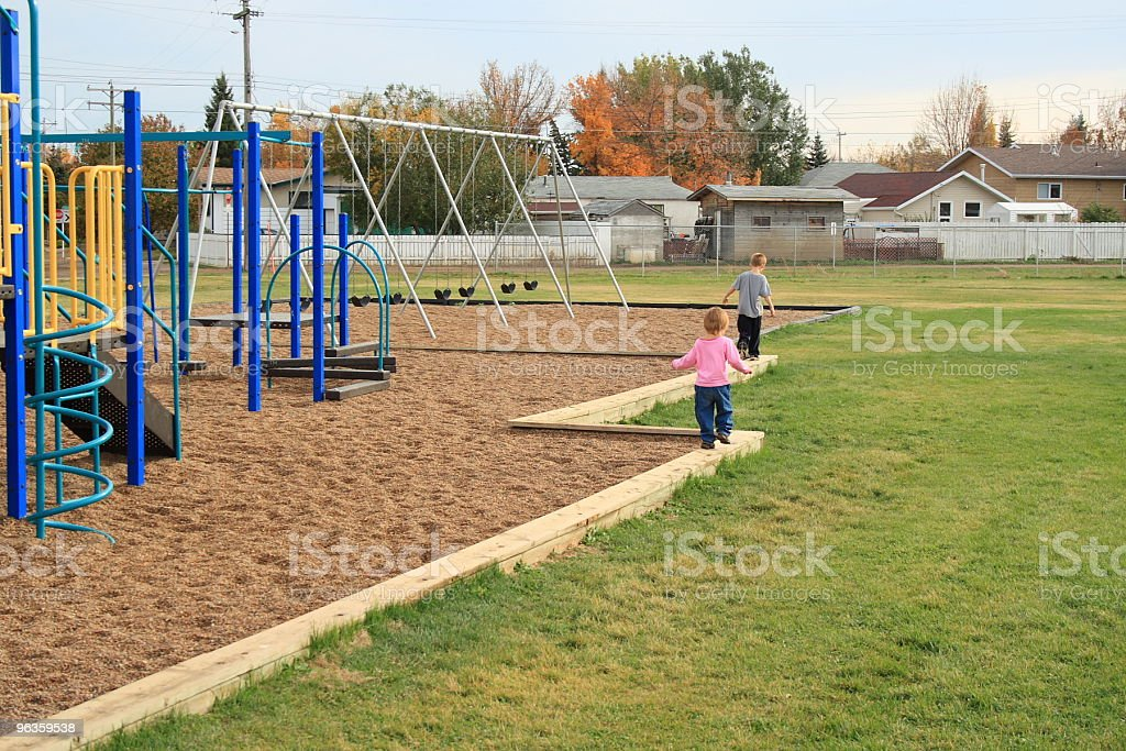 little girl follows her brother walking down beam at playground royalty-free stock photo