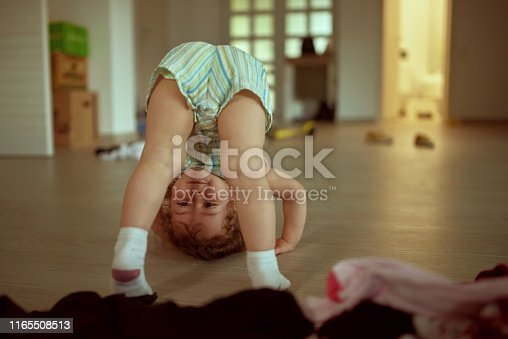 A little girl has fun and fools around the house, attempting to roll on the floor
