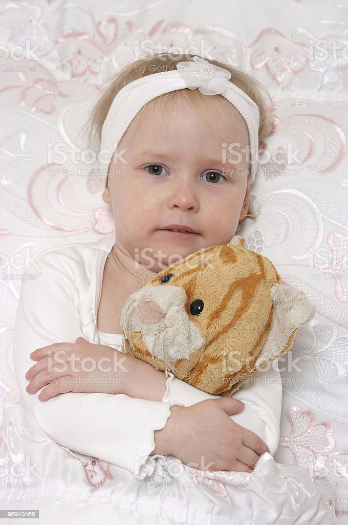 little girl, gathering to sleep on lacy bed royalty-free stock photo