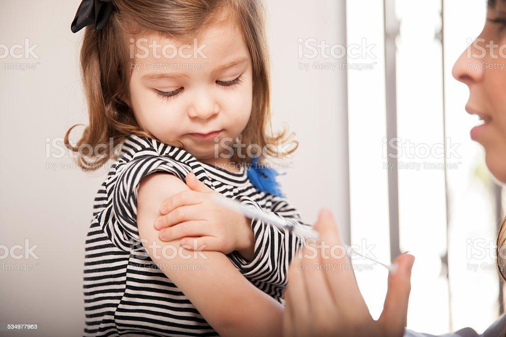 Little girl getting a flu shot stock photo