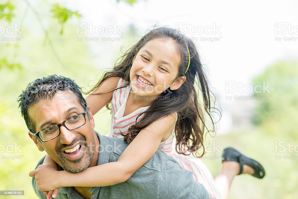 Little Girl Getting a Piggy Back Ride From Her Father royalty-free stock photo