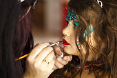 Profile view of make up artist applying face paint on little girl's face.