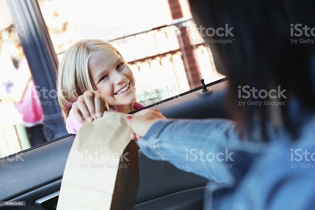 Little girl getting lunch bag from mom at school dropoff stock photo