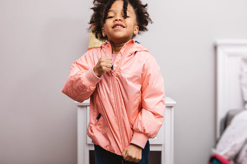 Little girl putting on her jacket to head out.