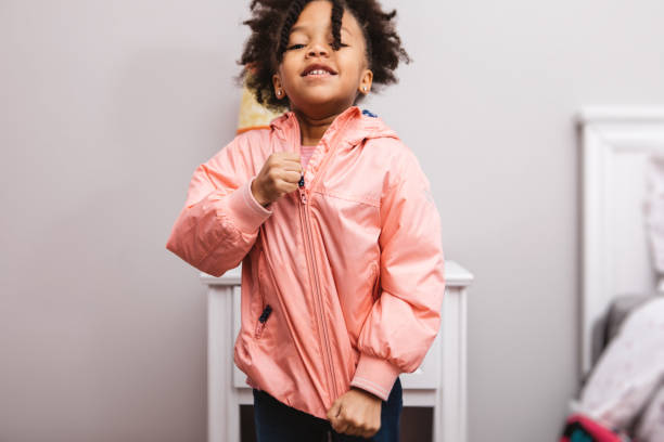 little girl getting ready for school Little girl putting on her jacket to head out. coat garment stock pictures, royalty-free photos & images