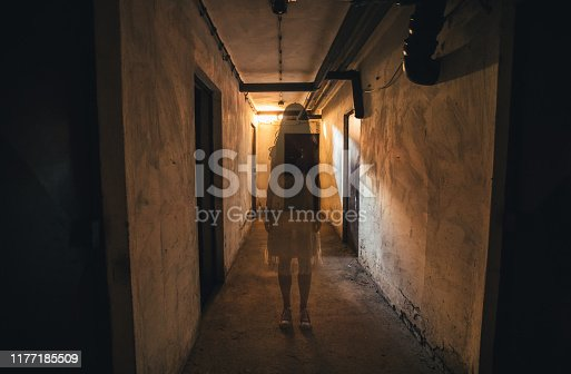 Scary girl in night gown in a dark basement hallway.