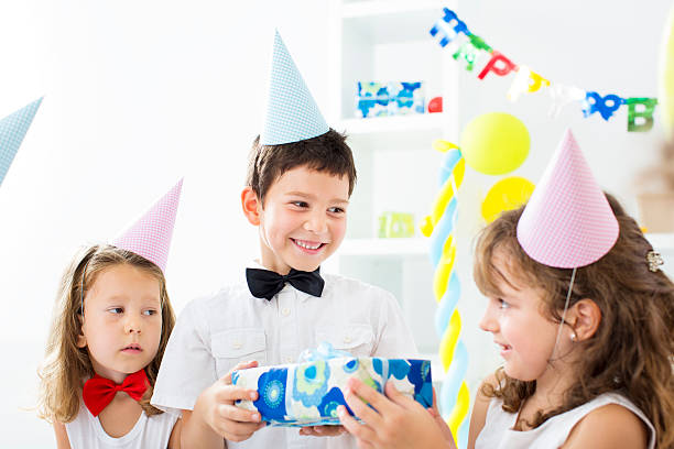 Little Girl Giving Birthday Present to Boy. Cute little girl giving birthday gift to her friend cute little boy, selective focus to cute little boy. group of friends giving gifts to the birthday girl stock pictures, royalty-free photos & images