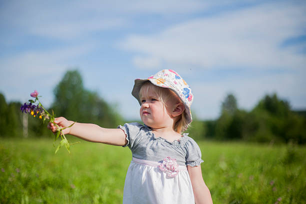 Little Girl Giving Bunch of Flowers stock photo
