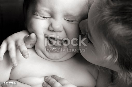 Little Girl Giving Her Baby Sister An Unwanted Kiss Stock Photo & More Pictures of 6-11 Months