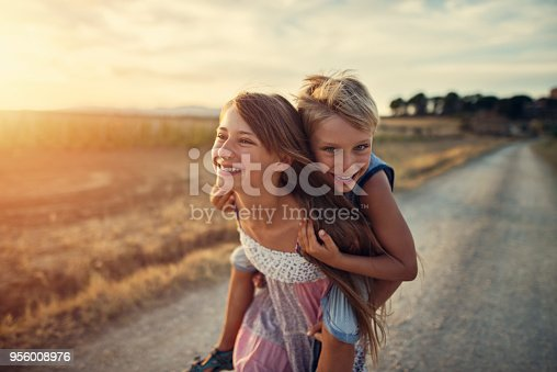 Little girl is giving her brother a piggyback ride. They are running on dirt road and laughing. Nikon D810