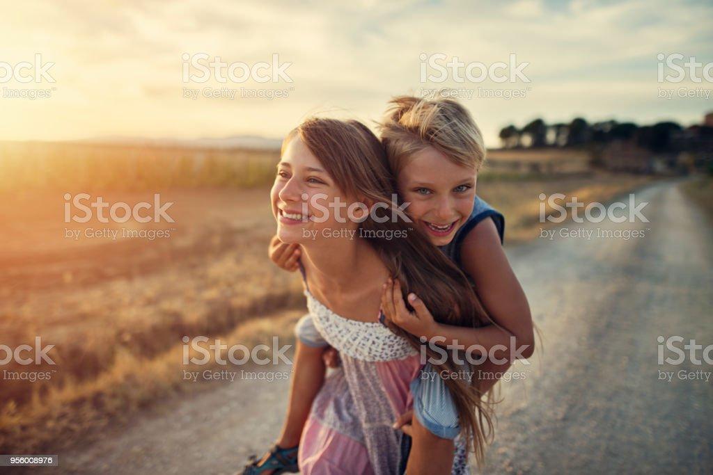 Kleines Mädchen geben ihrem Bruder eine Huckepack Fahrt – Foto