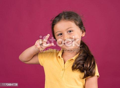 Little girl giving ok sign over pink background
