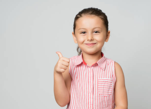 Little girl giving thumbs up stock photo