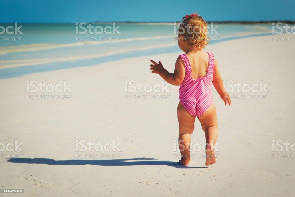 little girl go swim on tropical beach stock photo