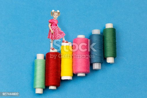 istock A little girl goes on coils with colored threads. 927444602