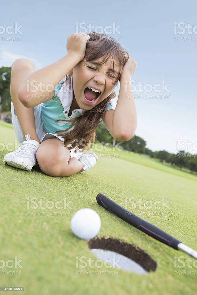 Little girl golfer disappointed after missing putt during golf game stock photo