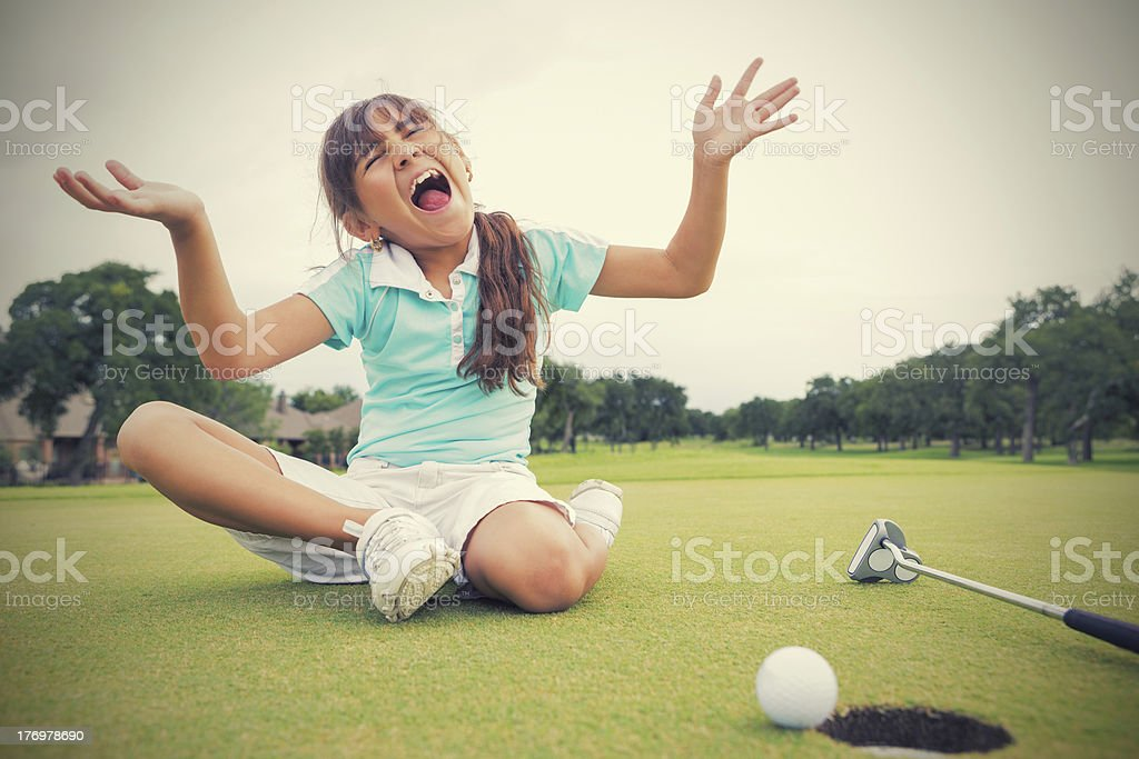 Little girl golfer distraught after missing putt on golf course royalty-free stock photo