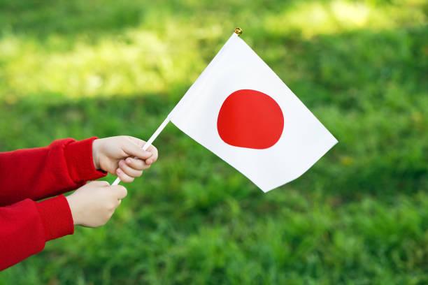 Kleine Mädchenhände halten Fahne – Foto