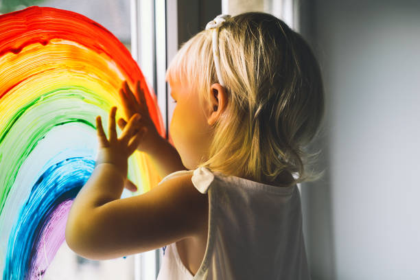 Little girl hands touch painting rainbow on window. Child Art and Creative. Kids leisure at home, childcare, safety joy symbol. stock photo