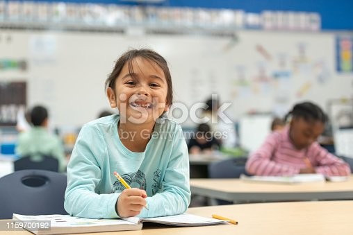 A cute little girl of african descent works hard on her in class assignment. She is working in her math workbook.