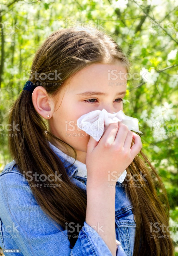 Little girl has allergy to spring blossoming and blowing her nose stock photo