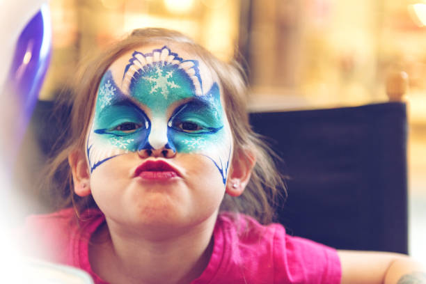 Little girl having a face paint stock photo
