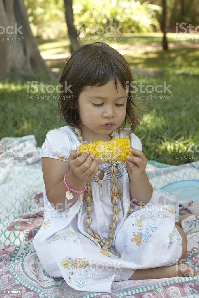 little girl having a picnic eating corn  royalty-free stock photo