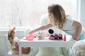 A little girl has a tea party with her doll and dog.