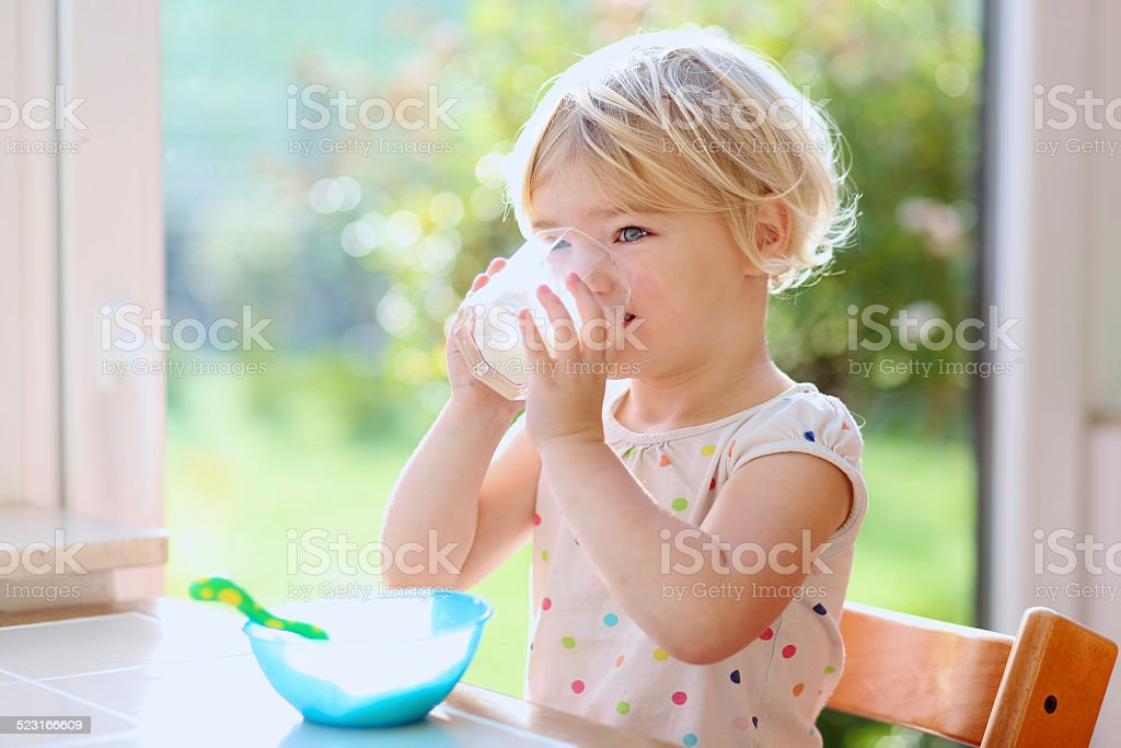 Little girl having breakfast indoors stock photo